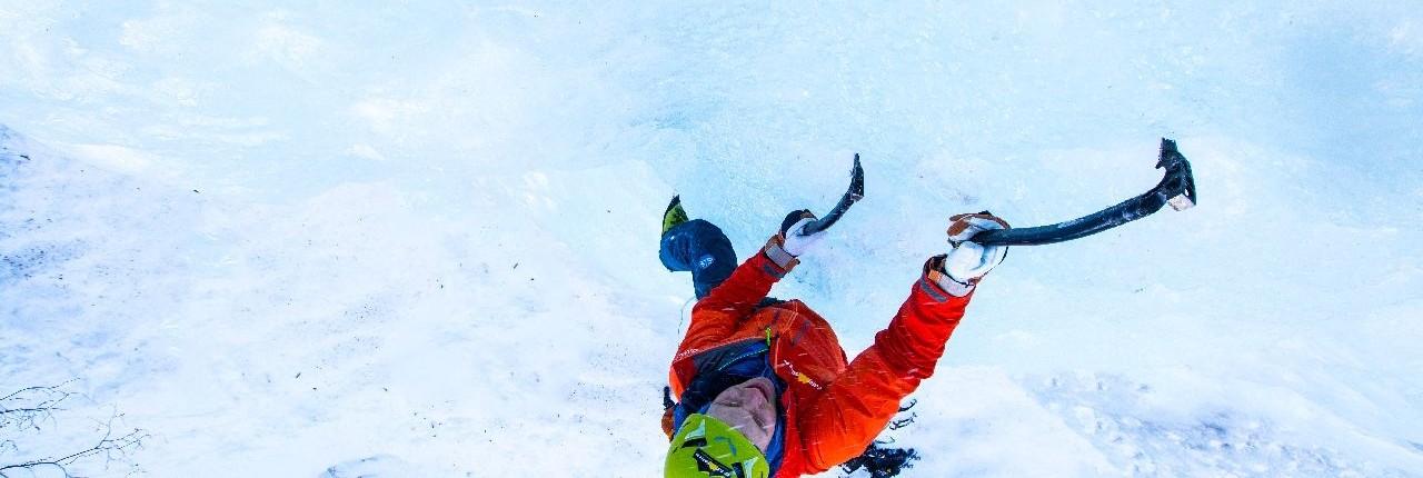 Mit Eispickel den gefrorenen Wasserfall klettern